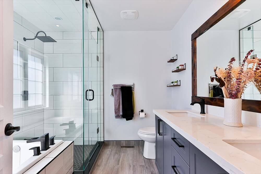 A bathroom with a his and her sink. There is a shower with a glass door. On the other side of the bathroom is a his and her sink with grey cabinets.