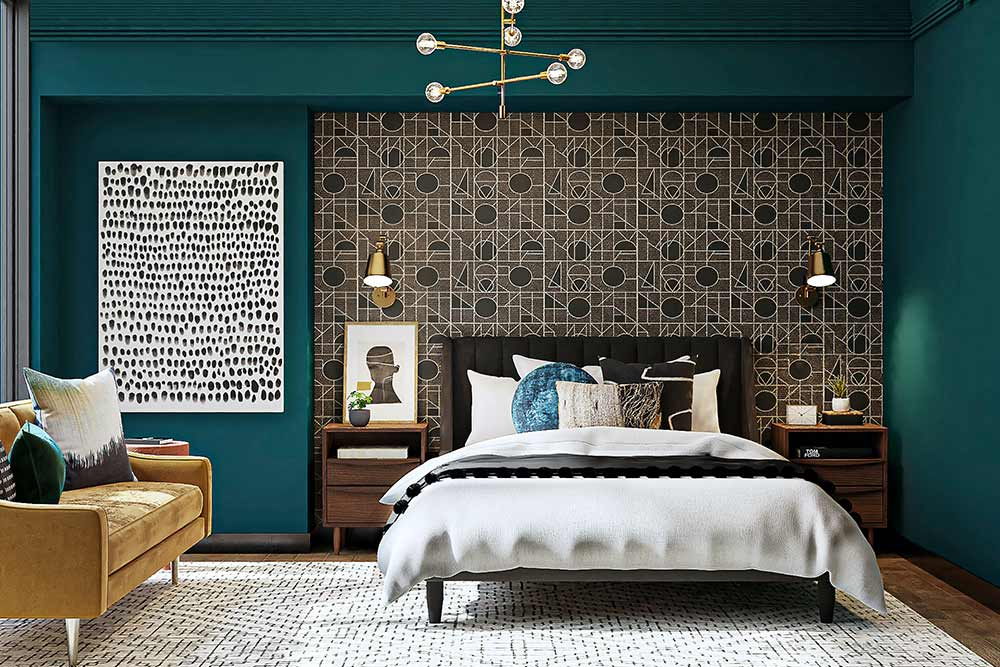 A bedroom with a geometric accent wall that is sunken into the back wall. The bed is decorated with a white and gray bedspread and a teal pillow. The outer accent wall is a teal green color. There is a large painting of black brush strokes in somewhat orderly columns. On the left of the room is a yellow couch with grey and white pillows as well as a teal accent pillow.