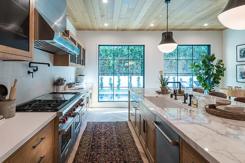 A photo of a large kitchen with wood flooring and updated premium appliances. JRC Housing specializes in construction, renovation, and remodeling in the Inland Empire region. We serve Los Angeles, Riverside, San Bernardino, and Orange counties, and offer free estimates.